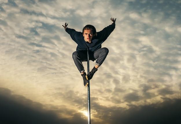 장대 댄스 맞는 남자 일몰에 야외에서 철 탑으로 운동