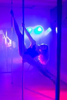 Pole dance. молодая стройная сексуальная женщина танцует на шесте в интерьере ночного клуба