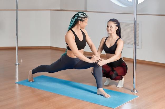 Тренер студии pole gym помогает женщине выполнять упражнения на гибкость и растяжку.