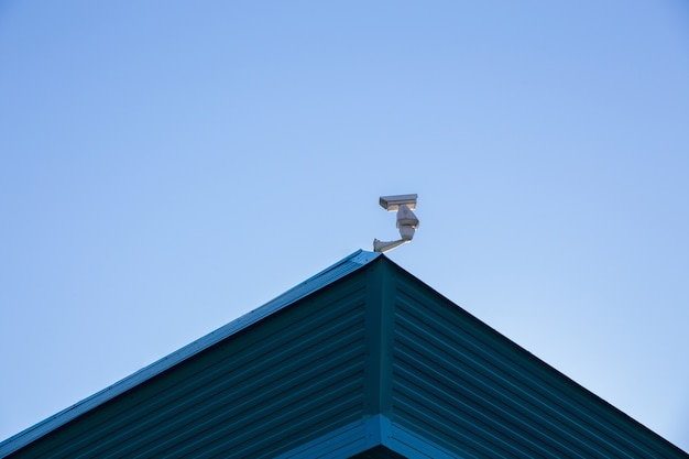 A pole with surveillance camera on the roof