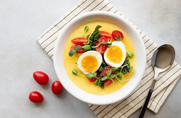 Миска поленты со свежими овощами, микрозеленью и яйцами на сером столе здоровый сбалансированный завтрак