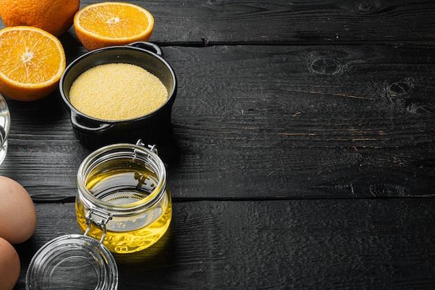 검정 나무 테이블 배경에 계란과 꿀이 있는 폴렌타 케이크 재료, 텍스트 복사 공간