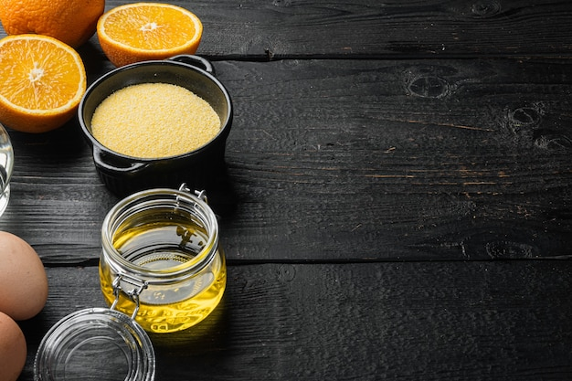 Polenta cake ingredients, with eggs and honey set, on black wooden table background, with copy space for text