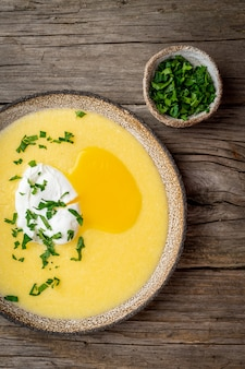 Polenta, porridge with parmesan cheese and poached egg, vertical on old dark wooden background