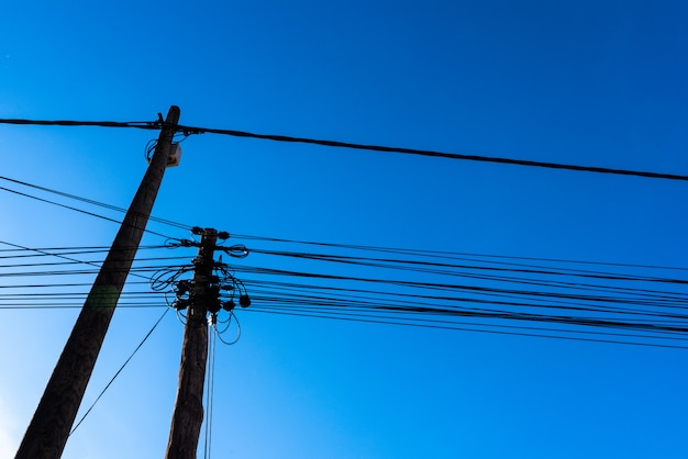 Poles with electricity and telecommunications cables seen from below against the blue sky background.
