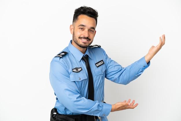 Полицейский мужчина кавказской изолирован на белом фоне, протягивая руки в сторону для приглашения приехать