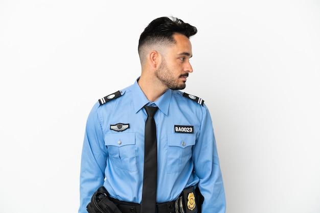 Кавказский человек полиции, изолированные на белом фоне, глядя в сторону