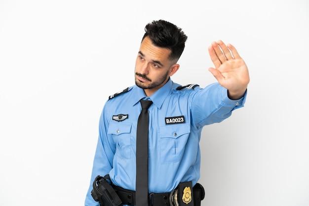 Кавказский человек полиции изолирован на белом фоне, делая жест стоп и разочарованный