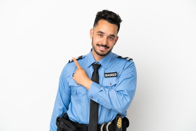 Полицейский мужчина кавказской изолирован на белом фоне, указывая в сторону, чтобы представить продукт