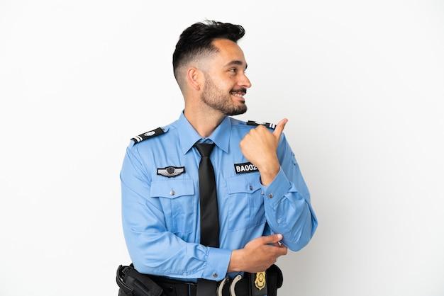제품을 제시하기 위해 측면을 가리키는 흰색 배경에 고립 된 경찰 백인 남자