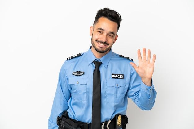 Полицейский мужчина кавказской изолирован на белом фоне, салютуя рукой с счастливым выражением лица