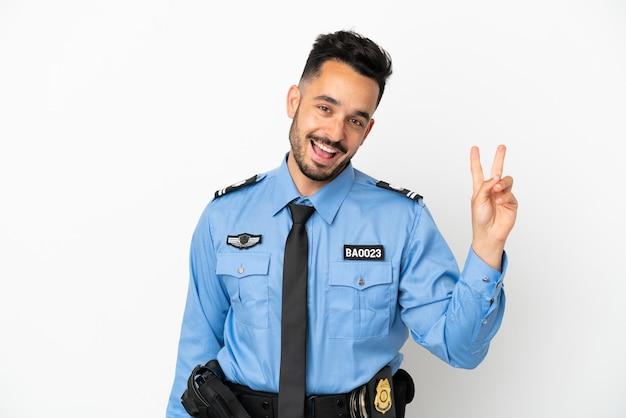 Кавказский человек полиции изолирован на белом фоне улыбается и показывает знак победы