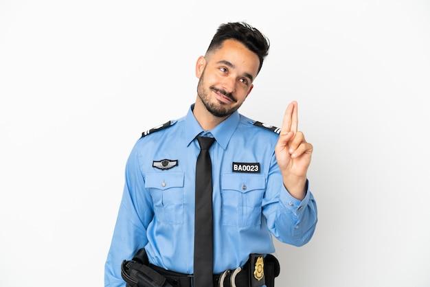 Полицейский мужчина кавказской изолирован на белом фоне со скрещенными пальцами и желает лучшего