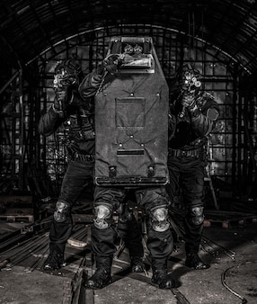 警察の対テロ作戦、反麻薬軍の戦術グループ、弾道シールドの後ろに隠れているswatチーム、武器を狙い、人質救助中に銃撃を反映しようとしている、接近戦の状況