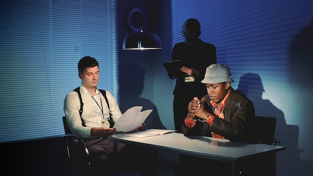 Police detective questioning suspect black man in interrogation room