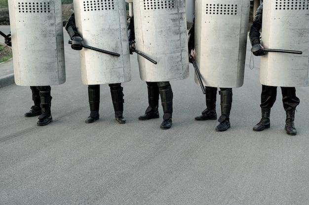폭동을 통제하면서 거리를 방패와 지휘봉으로 걷는 경찰