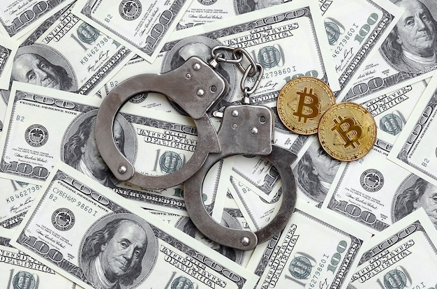 Police handcuffs and bitcoins lie on a large number of dollar bills