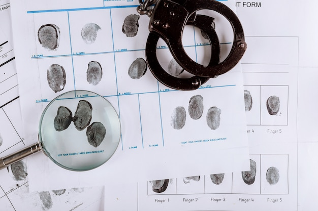 Police handcuffs and criminal fingerprints card, with magnifying glass, top view