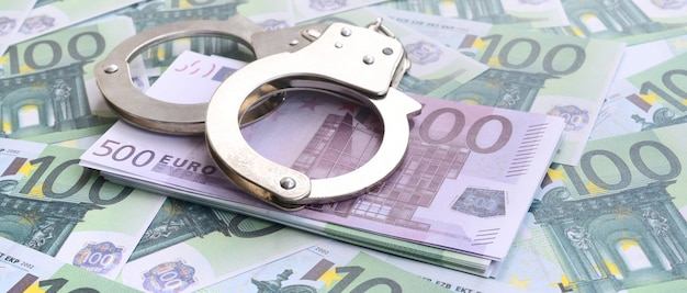 Police handcuffs lies on a set of green monetary denominations of 100 euros