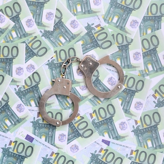 Police handcuffs lies on a set of green monetary denominations of 100 euros.