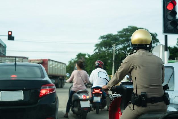 交通信号を待っているバイクに乗って警官