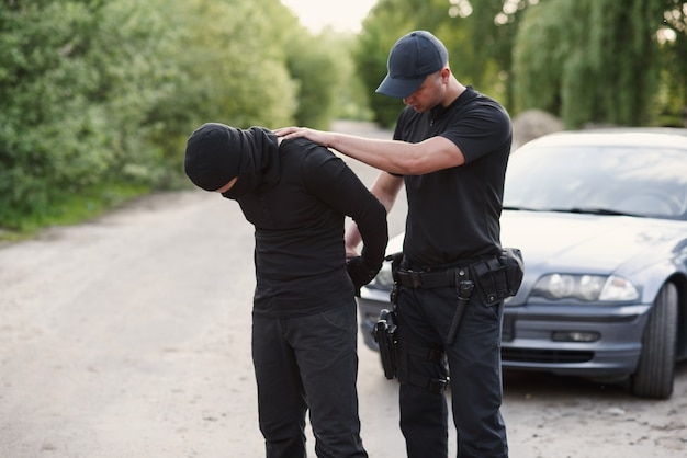 A police officer arrested an offender with the stolen car and handcuffed him close up.