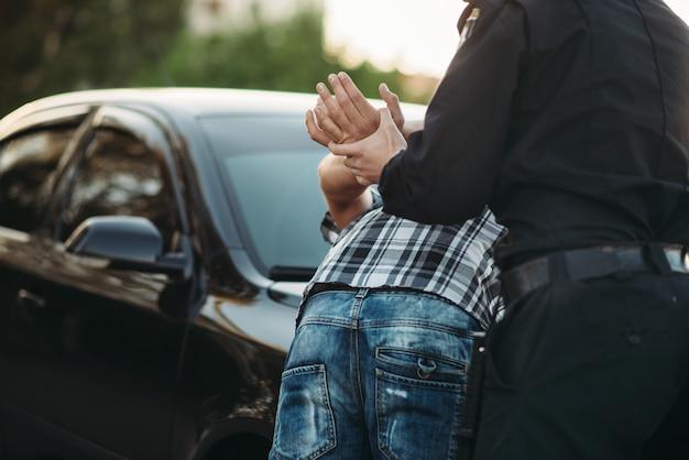 Сотрудник полиции задерживает водителя-нарушителя на дороге