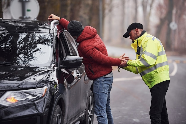 Police officer in green uniform caught automobile theft on the road.