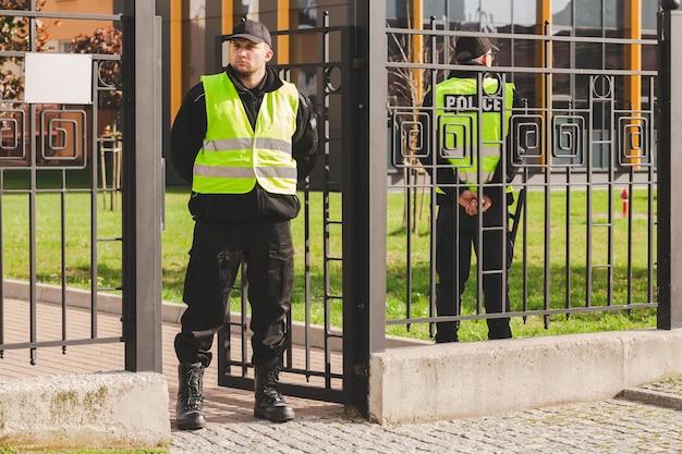 Офицер полиции в светоотражающем жилете стоит у входа в сквер
