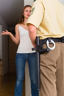 Police officer interrogation woman at front door