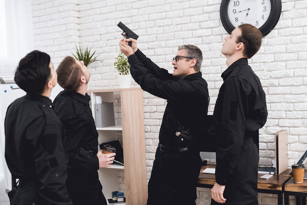 The police officer shows the subordinates how to use a gun.