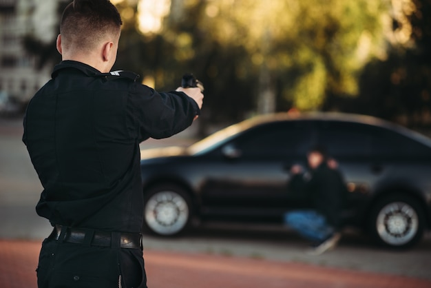 Police officer with gun arrests the car thief