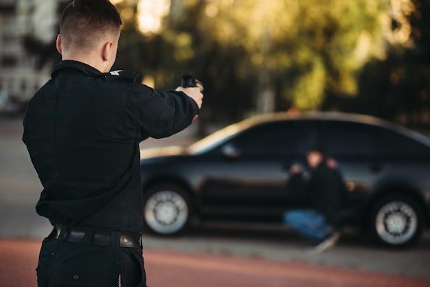 Полицейский с пистолетом арестовывает угонщика