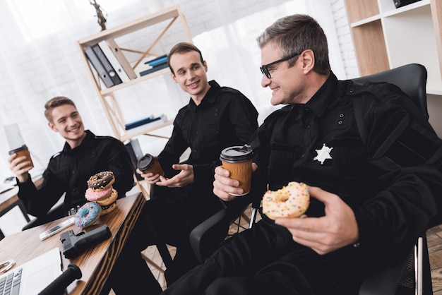 Police officers eat donuts and drink coffee in office.