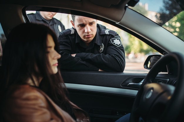 Полицейские в форме проверяют женщину-водителя