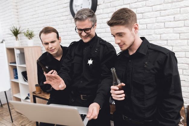경찰관들은 노트북을 함께 본다.