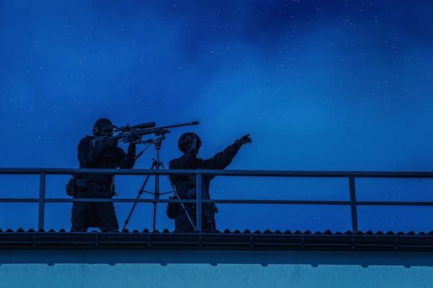 Снайперская команда полиции или армии, работающая с крыши здания города. снайперская пара-корректировщик обыскивает цель с помощью прибора ночного видения, указывает на активность в секторе стрельбы, корректирует огонь во время ночного вылета