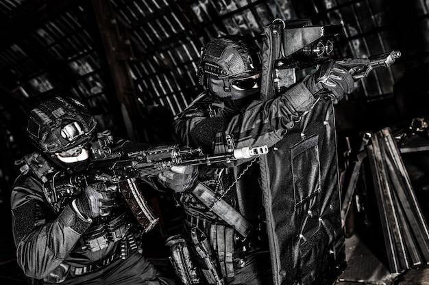 Полицейский спецназ, бойцы тактической группы по борьбе с терроризмом, охранники частной охранной компании, прицеливающиеся из оружия, продвигаясь вперед под прикрытием баллистического щита во время рейда по борьбе с наркотиками, ненасыщенные