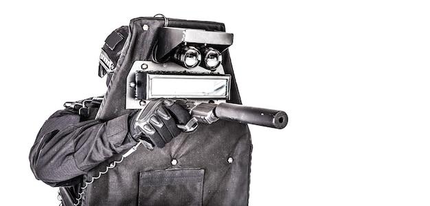 경찰 특수 작전 및 대테러 팀, 검은색 제복, 마스크, 헬멧을 쓴 swat 장교, 탄도 방패 뒤에 숨어 권총, 스튜디오 촬영, 흰색 배경에 격리