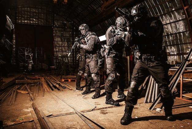 警察の特殊作戦の麻薬対策またはテロ対策チーム、黒いユニフォームとマスクの迅速な反応の戦術グループ、放棄された格納庫で慎重に動くセミオートマチックライフルで武装