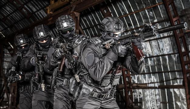 근접 전투 조건에서 소음이 나는 돌격 소총을 목표로 하는 분대장 뒤에서 스택 대형으로 움직이는 경찰 특수 작전 비상 대응 팀 전투기