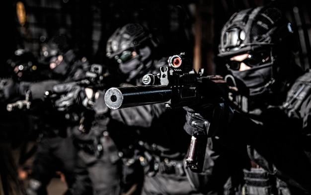 경찰 특수 작전, 검은 제복을 입은 신속한 대응 전술 그룹 구성원, 헬멧 및 마스크 뒤에 숨겨진 얼굴은 테러 대응 작전에 돌격 소총을 목표로 줄을 서서 서 있습니다.