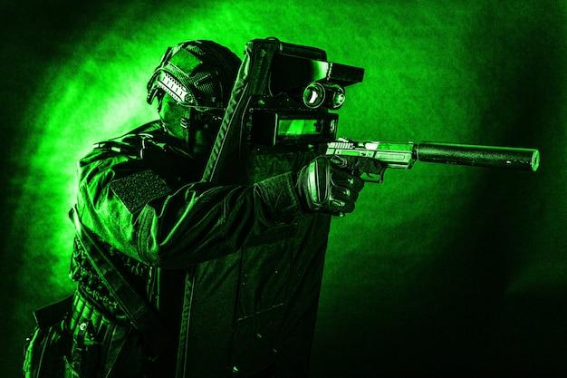 경찰 특수 작전 팀, 검은색 제복을 입은 신속한 대응 그룹 전투기, 방탄 방패 뒤에 숨어있는 동안 권총 장착 소음기로 조준하는 헬멧 및 마스크, 톤, 낮은 키 스튜디오 촬영