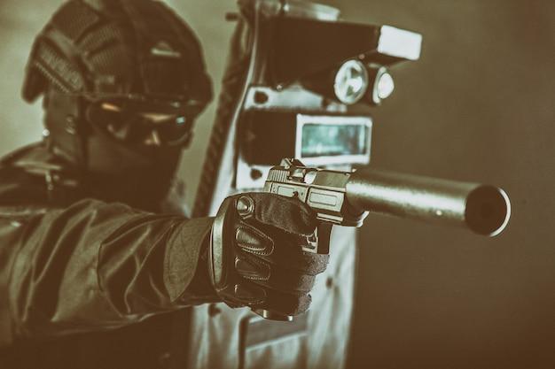 Полицейская группа специальных операций, боец группы быстрого реагирования в черной форме, в шлеме и маске, прицеливание с глушителем, оснащенным пистолетом, при этом прячется за баллистическим щитом, тонированное, сдержанная студийная съемка