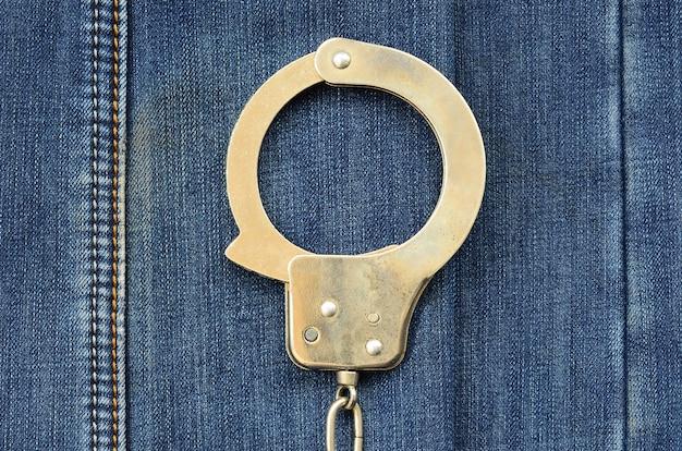 Police steel handcuffs lying on dark blue jeans background