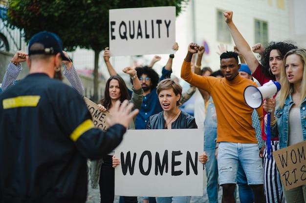 警察は、女性が行進する通りで抗議する上げられた握りこぶしで人々の活動家のグループを停止します