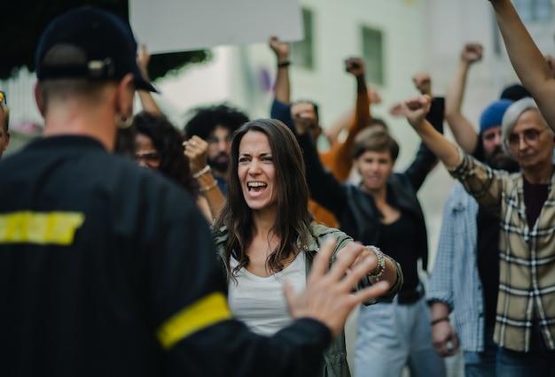 Полиция остановила группу кричащих активистов с поднятыми кулаками, протестующих на улицах