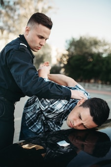 Policeman arrests the car thief on road