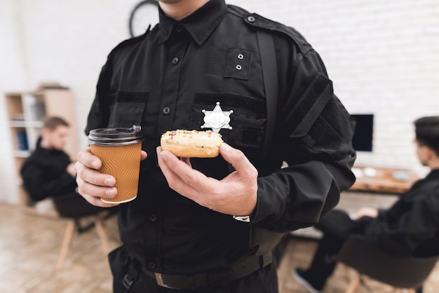 Policeman eating a donut and drinking coffee at dinner.