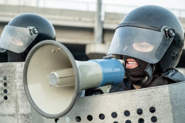 Полицейский в шлеме для массовых беспорядков держит щит и отправляет сообщение через громкоговоритель во время разговора с террористом протестующих